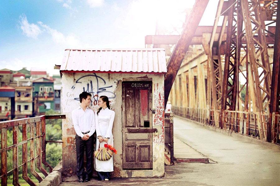 Happy young couple on Long Bien Bridge - Hanoi travel guide