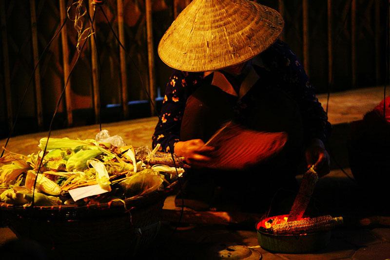 A street vendor with grilled corn in Hanoi Old Quarter - Hanoi street food tour